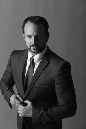 Businessman wears smart suit and tie. Leader unbuttons jacket Stock fotó