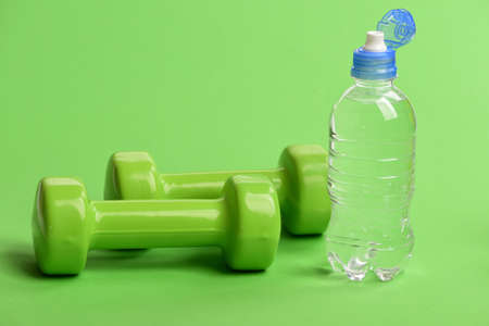 Water bottle near lightweight barbells, close up. Athletics concept