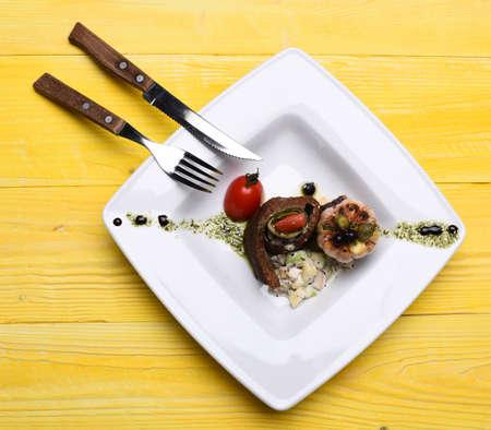 Baked pork steak in circle on salad near tomato Stock Photo