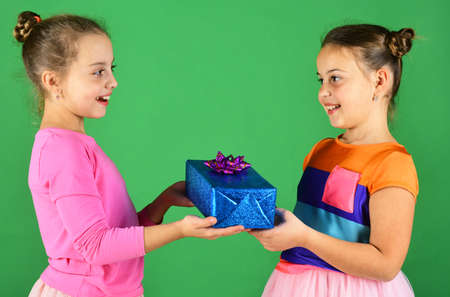 Children with happy faces pose with presents on green background