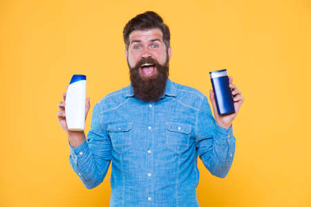 Grooming at every opportunity. Bearded man hold shampoo bottles yellow background. Cosmetics and toiletries. Hygiene and personal grooming. Male body grooming and skincare. Grooming products for men Imagens