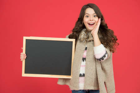 Profitable deal. Happy girl blank blackboard. copy space. Important information. Winter activity advertisement. Time for winter holiday. Useful info. Winter shopping sales. Announcement board