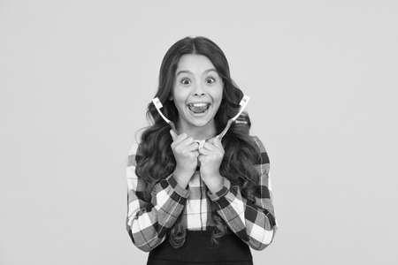 Child school girl smart kid happy face cares hygiene. Brush teeth concept. Teeth hygiene. Teeth whitening. Girl cute long hair holds toothbrushes yellow background. Child girl holds two toothbrushes