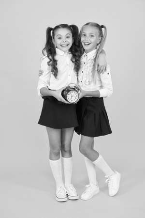 Schoolgirls and alarm clock. Children school pupils adorable formal uniform outfit. Kids hold alarm clock counting time. Time for break and relax. Alarm ringing. Time for lunch. School schedule