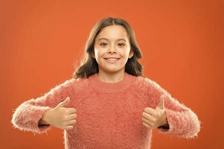 international childrens day. successful little girl smiling. small kid autumn sweater. feel comfortable in casual fashion. cheerful child hold thumb up. carefree childhood. her healthy smile