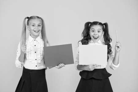 Children presenting own projects. Explain main point. Girls school uniform hold poster. Visual communication concept. School friendship. School girls show poster. Presentation poster copy space