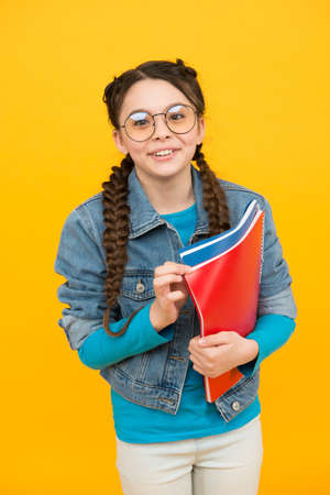 Happy child hold books yellow background. 写真素材