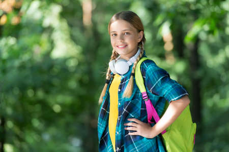 Happy child carry backpack natural outdoors.