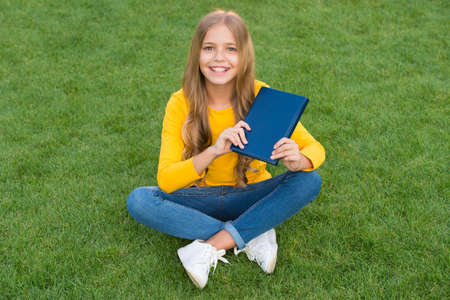Girl reading book outdoors green lawn background, books shop concept