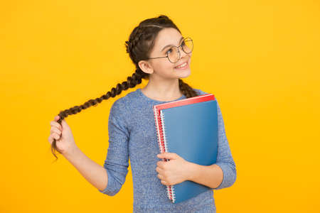 Flights of imagination. Girl with long plaits hold books. Little dreamer with thoughtful look yellow background. Imagination and fantasy. Developing imagination. Learning with imaginaiton matters