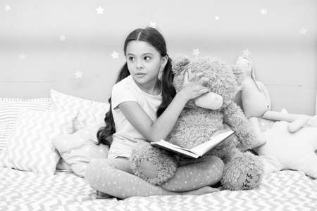 Home reading. Cute literature reader in bedroom. Little child read book to teddy bear toy. Childrens literature. Studying english language and literature. Book and literature promotion. Home library 写真素材