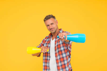 Man spraying disinfectant camera like weapon, cleaning day concept
