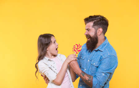 One for me none for you. Father take lollipop from unhappy child. Fighting for swirl lollipop on stick. Sweet food. Dessert snack. Candy shop. Sweetshop and confectionery. Cant wait to lick lollipop