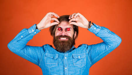 Restaurant cuisine. dieting and healthy lifestyle. happy bearded man with sweet cherry. cherries for breakfast. cheerful male hipster hold fresh berry. fruit full of vitamin. only organic food
