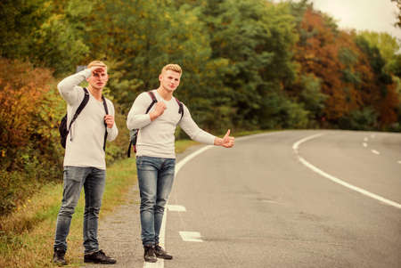 Missed their bus. Need help. Cheap transport. Transport problem. Try to stop some car. Travel and transport concept. Twins men at edge of road nature background. Reason people pick up hitchhikers Foto de archivo