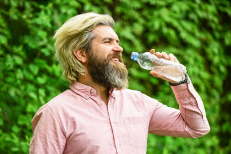 Refreshing lemonade. Soda water. Water balance. Man bearded tourist drinking water plastic bottle nature background. Summer heat. Thirsty guy drinking bottled water. Healthy lifestyle. Hot day