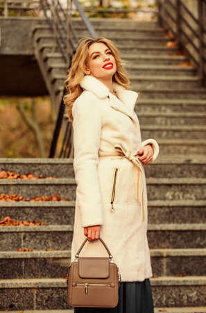 Finally here. girl warm coat stairs background. faux fur coat fashion. stylish business lady leather bag. glamour girl look luxuriously. sexy blong woman red lipstick. autumn season. european winter