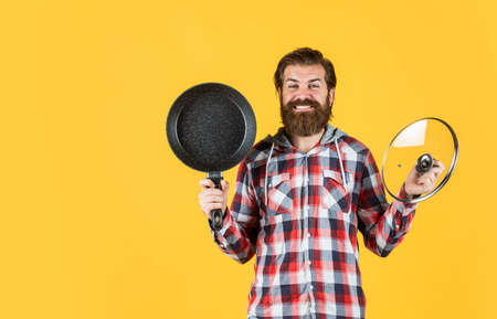 bearded man hold kitchen pan. brutal hipster cooking with saucepan. housekeep husband cook in pot. mature chef in checkered shirt. prepare meal food at home. professional cook