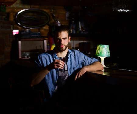 Guy at bar counter drinks glass of shot or liqueur. Reklamní fotografie