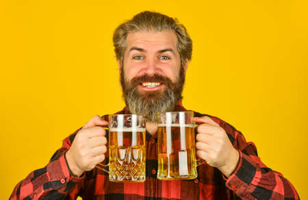 lifestyle concept. brutal hipster drink beer. mature bearded barman hold beer glass. confident bartender raising toast. leisure and celebration. Man drinking beer in pub bar. Beer with foam
