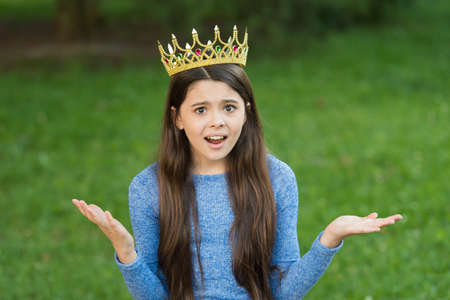 Cute girl golden crown outdoors green nature background, confusing expression concept