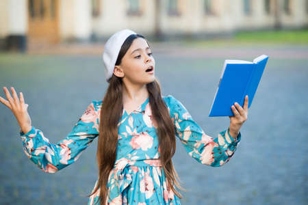 Girl student reading book outdoors, recite poetry concept