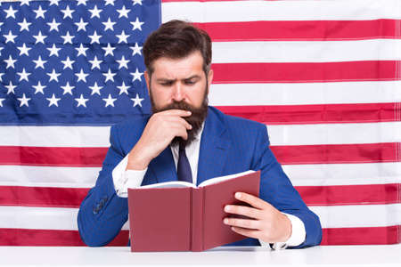Read explanation to learn more. Teacher read book on USA flag background. Teaching to read. Literacy study. School and education. Language courses. American English. Read and understand 写真素材