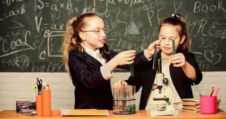 Educational experiment concept. Girls classmates study chemistry. Microscope and test tubes on table. Perform chemical reactions. Basic knowledge of chemistry. Make studying chemistry interesting