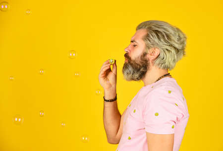 Blow inflate bubbles. Forever young guy. Positive. Infantility concept. Carefree man soap bubbles.