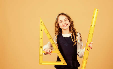 School student learning geometry. Pupil girl with big rulers. small girl back to school.