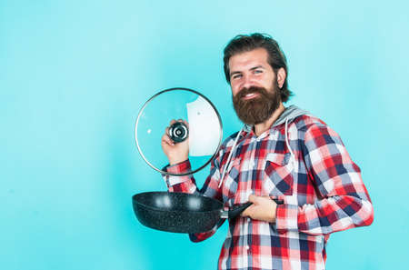 Professional chef man cook in checkered shirt. bearded husband. Restaurant. Enameled cast iron cooking vessels. Nonstick pan coated. Cooking healthy food Stock Photo