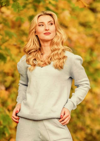 Sporty girl. Woman enjoy autumn season in park. Warm knitwear. Girl relaxing in nature wearing knitwear suit. Clothes for rest. Feel practicality and comfort. Model knitwear clothes leaves background