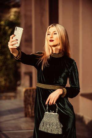 Loving her new style. fashion blog. elegant woman green velour dress. glamour velvet textile.   businesswoman make selfie on phone. modern life. girl care gem stone handbag. glam clutch accessory Stock fotó