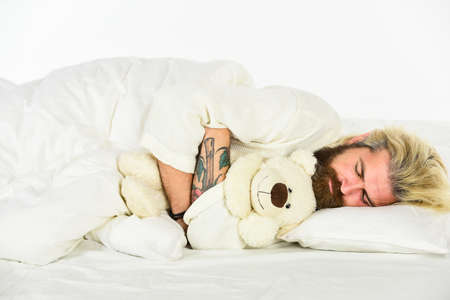 Cute teddy bear toy. Create sleep positive bedroom environment. Playful adult. Cute and romantic. Bearded hipster play toy. Man hug soft toy relaxing in bed. Lovely hipster. Make surprise concept Standard-Bild
