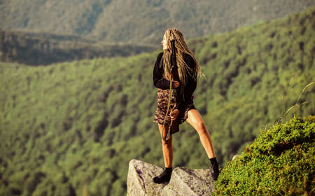 Feminist girl. Hunting season. She is warrior. Woman attractive long hair pretty face hold rifle for hunting. Dangerous girl. Defending concept. Warrior mountains landscape background