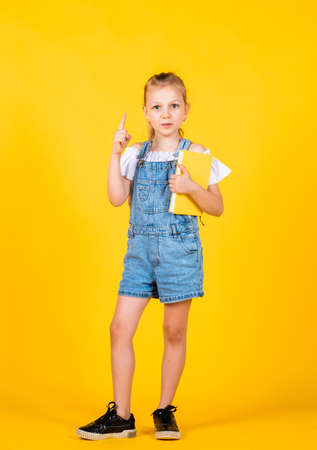 having new idea. Girl read the book. Back to school and childhood concept. Pupil on yellow background. Kid with smart look and casual outfit. modern education concept. inspired with idea Standard-Bild