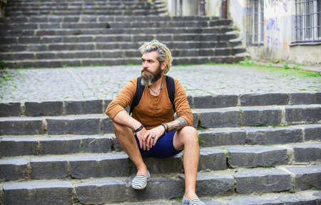 Explore the back streets. Bearded hipster relax outdoors. Man tourist sit on stairs. Man with beard and moustache relaxing urban space. Tourism concept. Underground culture. Hidden touristic gem
