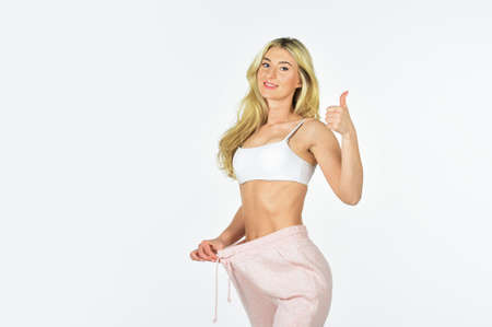 Satisfied fitness lady. Dieting and fitness. Girl slim belly. Slim fit attractive woman. Girl diet lost weight white background. Healthy body. Stunning results. Loss weight concept. Healthy lifestyle