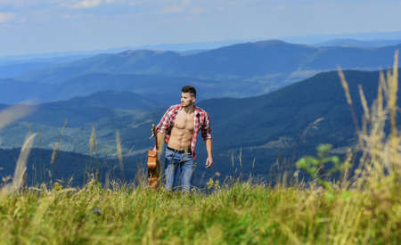 Carefree wanderer. Vast expanses. Peaceful hiker. Conquer the peaks. Man hiker with guitar walking on top of mountain. Guy hiker enjoy pure nature. Musician hiker find inspiration in mountains