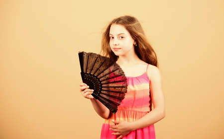 small girl with lace black fan. fashion accessory. elegant little lady. beauty and fashion. little girl with long hair. happy childhood. hot summer. small girl child use fan. hot summer weather. Standard-Bild