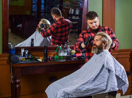 Styling hair. Near impossible to modify proceedings. Hipster getting haircut. Man with dyed hair. Barber hairstyle barbershop. Barber cosmetics. Hairdresser tools. Barber busy concentrated on process