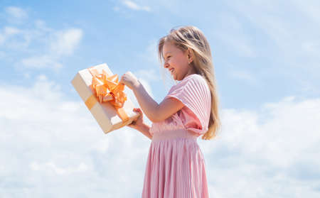 Perfect day. Holding gift in hand. Smiling little girl with shopping gift. Black Friday sale. holidays concept. international childrens day. Joyous female kid holding gift-wrapped box
