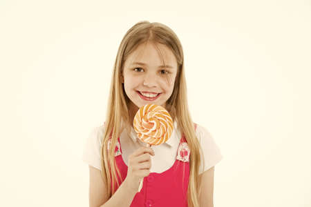 Girl eating big candy on stick or lollipop. Sweet tooth concept. Girl on smiling face holds giant colorful lollipop in hand, isolated on white background. Kid with long hair likes sweets and treats