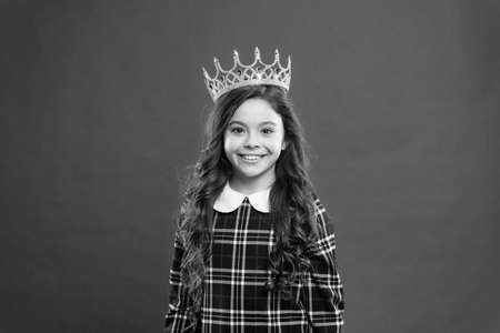 Every girl dreaming to become princess. Lady little princess. Girl wear crown red background. Monarch family concept. Princess manners. Monarch attribute. Kid wear golden crown symbol of princess Stockfoto