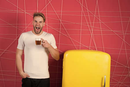 Man sleepy yawning hold morning drink near refrigerator. Bachelor hold cup of tea or coffee at retro fridge on pink background. Morning tea ideas and recipes. Morning teas to jump start your day 스톡 콘텐츠