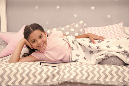 Satisfied with happy end. Girl child lay bed read book. Kid prepare to go to bed. Pleasant time in cozy bedroom. Girl kid long hair cute pajamas relax and read book. She likes kind stories about love Banque d'images