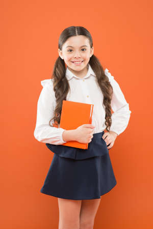 Interesting book for children. small girl in school uniform. get information form book. schoolgirl writing notes on orange background. Homeschooling concept. interesting story for happy girl