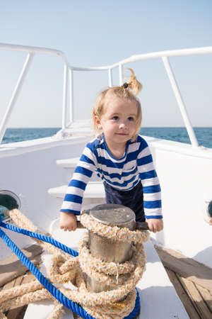 funny kid in striped marine shirt. small sailor on boat. summer vacation. childhood happiness. journey discovery. Transportation. happy small boy on yacht journey. Sea journey. journey concept