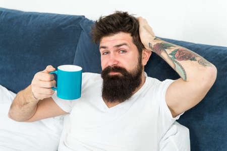 Tune in to new day. Morning awakening better with cup coffee. Relax and rest. Humanity runs on coffee. Man brutal handsome hipster relaxing bedroom drink coffee. Bearded guy enjoy morning coffee