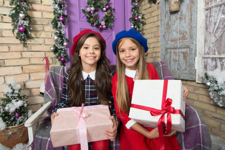Santa visits us only once a year. Cute children with new year presents. Merry Christmas and Happy New Year. Happy little girls hold gift boxes. Festive preparation for Christmas and New Year at home